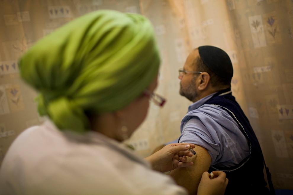 18. Израильская медсестра делает мужчине инъекцию против вируса H1N1 в иерусалимской клинике в среду 4 ноября 2009 года. (AP Photo/Bernat Armangue)