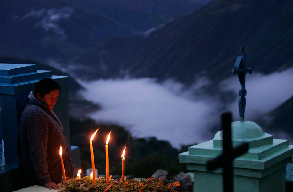 19. Женщина на могиле своего сына на кладбище Мазатлан Вилла де Флорес в День мертвых в Оахаке, Мексика, 1 ноября 2009 года. (REUTERS/Jorge Plata)