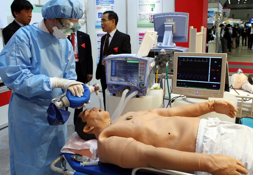 20. Врач в полном защитном костюме вставляет трубку в горло манекену, созданному специально, чтобы помочь врачам распознать вирус H1N1 на выставке «Security & Safety Trade Expo» в Токио в четверг 22 октября 2009 года. Этот гуманоид в полный человеческий рост был разработан компанией «Medical Education Technologies, Inc.» - крупнейшим в мире поставщиком симуляторов пациентов – чтобы помочь медикам распознать симптомы болезни и научиться лечить пациентов. Робот может потеть, стонать, плакать и биться в конвульсиях, как обычный человек с вирусом H1N1. И если роботу вовремя не помочь, симптомы ухудшатся, и он перестанет дышать. (AP Photo/Koji Sasahara)