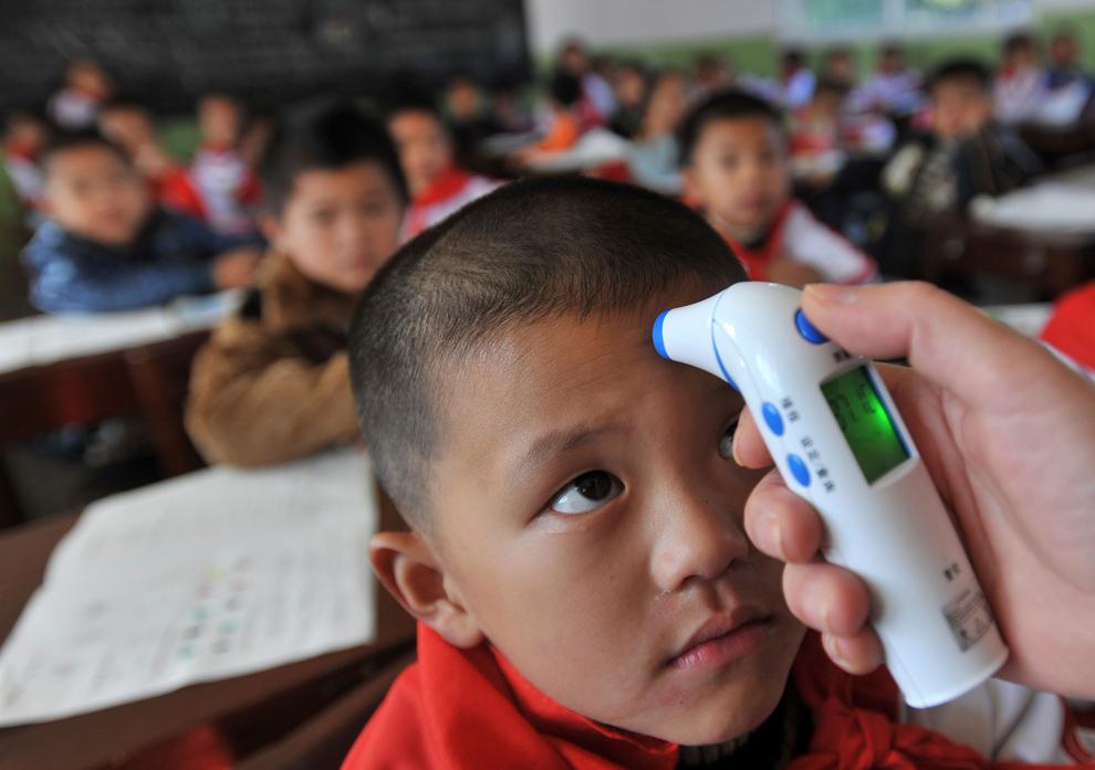 24. Учитель меряет температуру школьника в целях профилактики свиного гриппа в начальной школе в Ухане, провинция Хубэй, в понедельник 2 ноября 2009 года. (AP Photo)