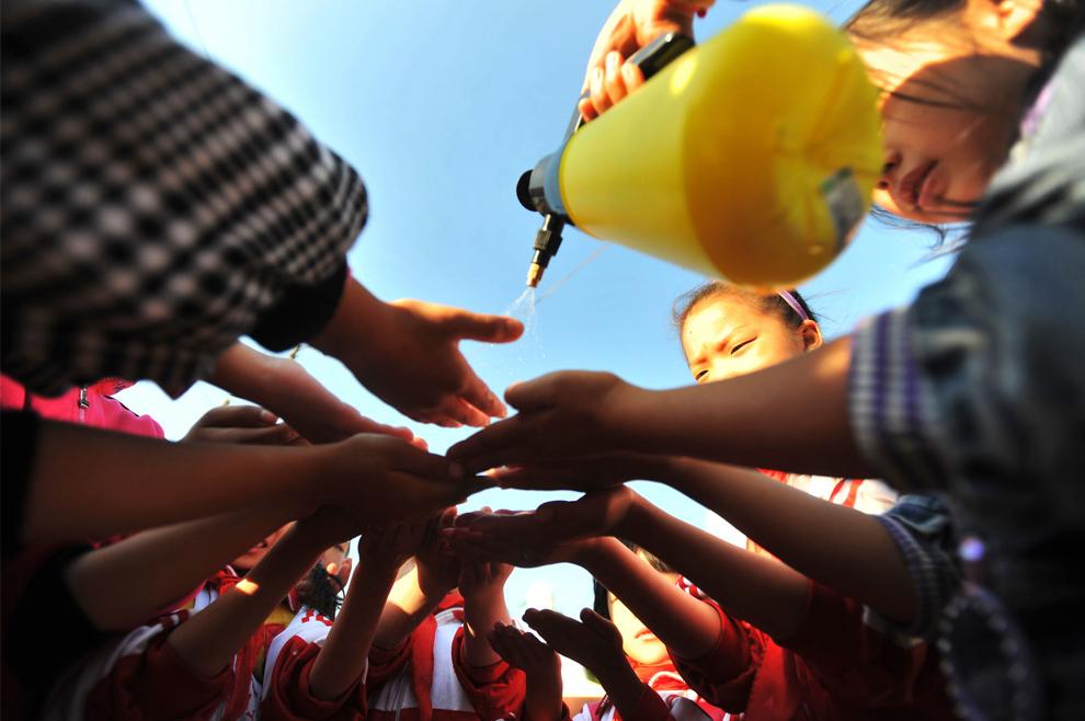 27. Учитель брызгает спиртом на руки школьникам во время профилактики распространения вируса гриппа H1N1 в начальной школе в Ухане, провинция, Хубэй, Китай, 2 ноября 2009 года. (AP Photo)