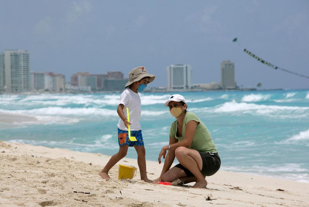 30. Кевин Солис и его мать Абди Сантойо в масках против вируса свиного гриппа на пляже в Канкуне, Мексика. (AP Photo/Israel Leal )