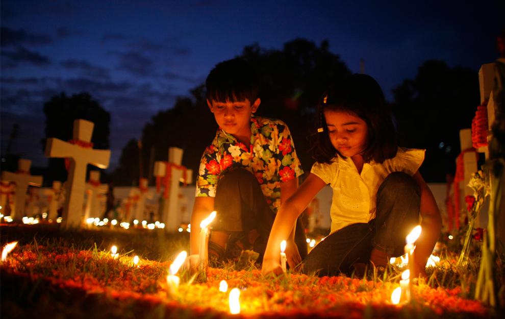 32. Дети зажигают свечи во время молитвы усопшим в День всех святых на кладбище в церкви Холи Розари в Дакке, Бангладеш, 2 ноября 2009 года. (REUTERS/Andrew Biraj)