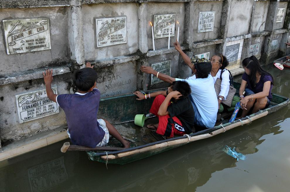 35. Филиппинская семья использует самодельный плот, чтобы проплыть по затопленному кладбищу в пригородном районе Ангоно к востоку от Манилы 1 ноября 2009 года. Миллионы филиппинцев по всей стране пришли на кладбища, чтобы почтить память об усопших в День всех святых, через день после тайфуна Миринэ, ставшего причиной гибели, по меньшей мере, 14 человек. Ливни и сильные ветры Миринэ также усложнили чрезвычайные ситуации для десятков тысяч и без того бездомных людей, лишившихся крова в двух предыдущих ураганах, погубивших более 100 человек за 5 недель. (JAY DIRECTO/AFP/Getty Images)