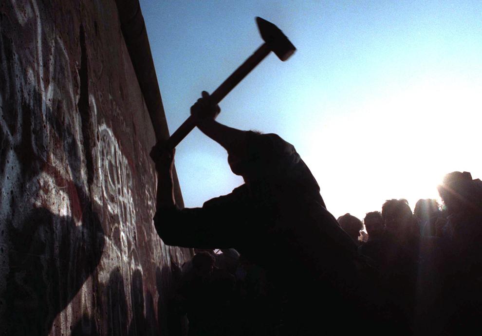 2. На этом фото человек бьет молотом Берлинскую стену 12 ноября 1989 года после того, как граница между Восточной и Западной Германией была снесена после 28 лет. (AP Photo/John Gaps III)