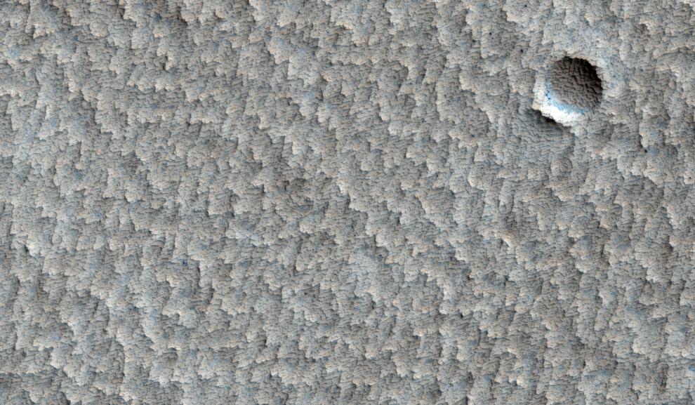 2. Разрушенный кратер на зубчатой поверхности огромной равнины недалеко от вулкана Павонис на Марсе. (NASA/JPL/University of Arizona)
