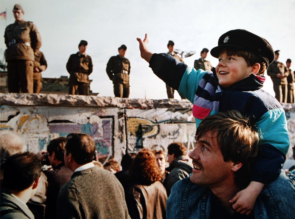 3. Мальчик машет солдатам на Берлинской стене перед Бранденбургскими воротами 10 ноября 1989 года. (John Tlumacki/Boston Globe staff)