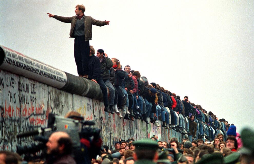 4. Люди стоят на части Берлинской стены на Потсдамской площади, которая была открыта. утром 11 ноября 1989 года. (John Tlumacki/Boston Globe staff)