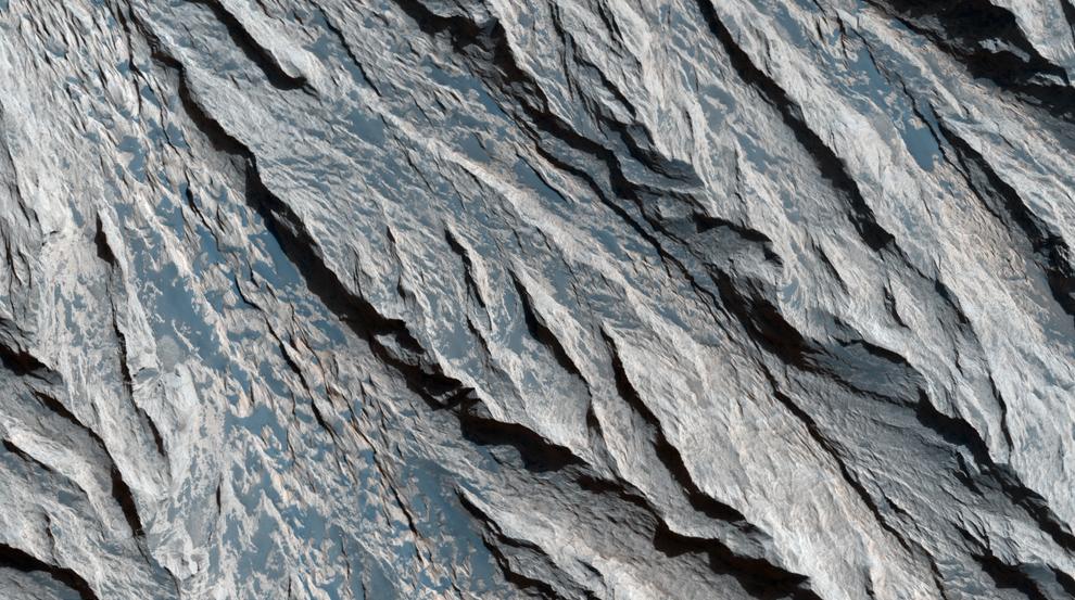 5. Слои и минералы в долине Кандор Хазма. На этом снимке вы видите утес вдоль светлого отложения в долине Маринера. Ветряная эрозия образовала V-образные узоры по краям многих слоев. (NASA/JPL/University of Arizona)