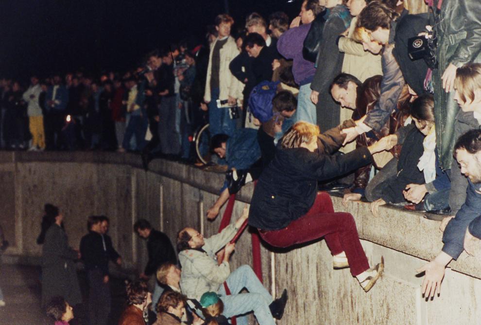 6. Жители Восточного Берлина помогают жителям Западного забраться на стену 10 ноября 1989 года. (AP Photo/Jockel Finck)