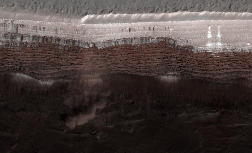 6. Лавины на откосах на северном полюсе Марса. Материал, включающий в себя лед и пыль и, возможно, большие валуны, откалывается от нависшего утеса и каскадом сходит с более мягких скатов. Это отложение составляет примерно 180 метров в диаметре и растягивается на 190 метров от основания утеса. (NASA/JPL/University of Arizona)