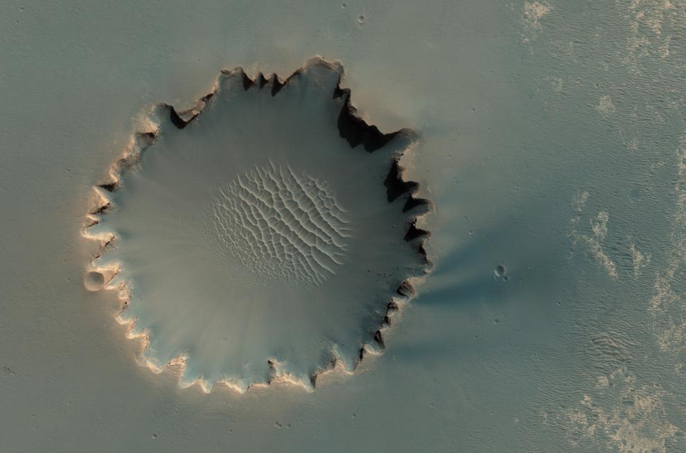 8. Кратер Виктория в Meridiani Planum. Кратер составляет примерно 800 метров в диаметре. Слоистые осадочные породы отложились вдоль внешней стены кратера, а на дне кратера видны валуны, отколовшиеся от стены кратера. В пределах стен этого кратера взорвался марсоход НАСА. (NASA/JPL/University of Arizona)