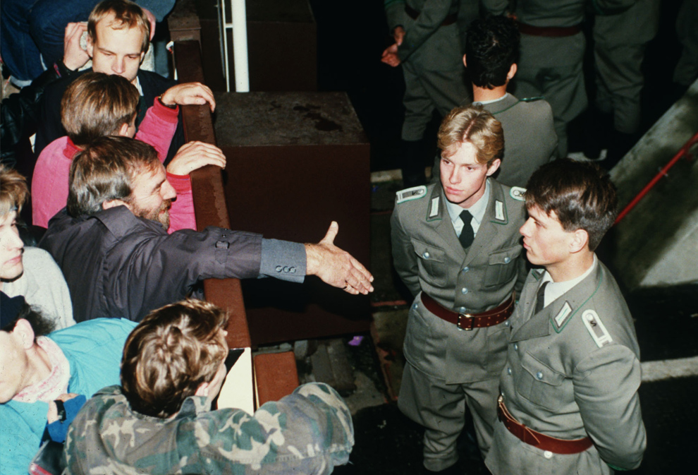 8. Пограничные полицейские Восточной Германии отказываются от рукопожатия берлинца, стоя на восточной стороне рядом с чекпойнтом Чарли 10 ноября 1989 года после открытия границы. (AP Photo/Lutz Schmidt, File)