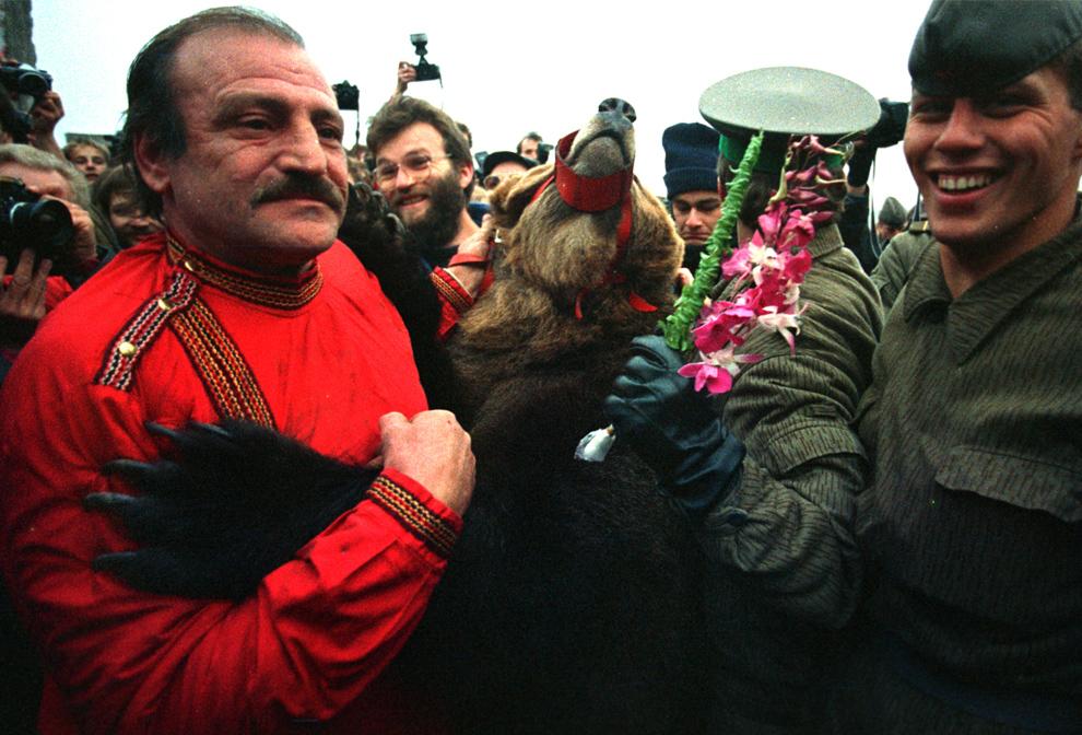 9. Цирковой медведь на задних лапах пересекает границу Западного Берлина через снесенную часть стены на Потсдамской площади 11 ноября 1989 года. (John Tlumacki/Boston Globe staff)
