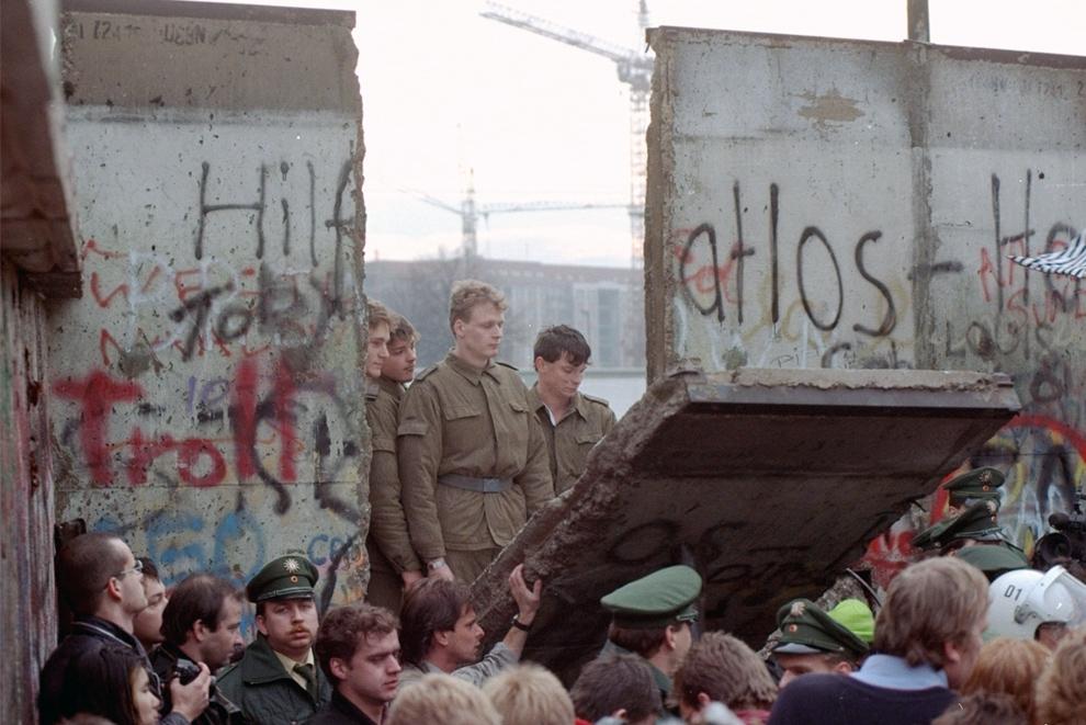 10. Солдаты пограничной службы Восточной Германии в проеме снесенной демонстрантами части стены в Бранденбургских воротах 11 ноября 1989 года. (AP Photo/Lionel Cironneau)