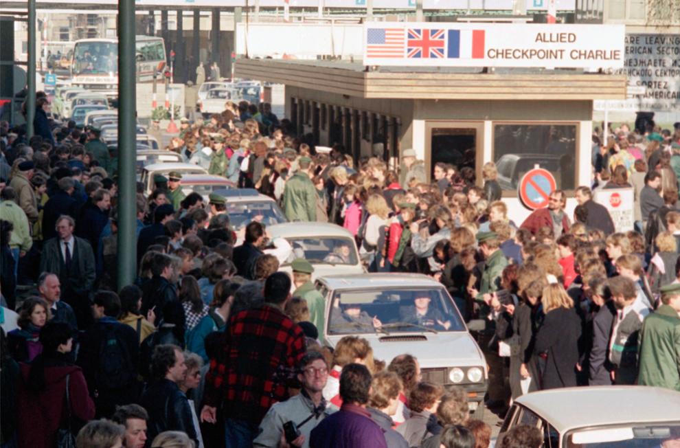 11. Жители западной Германии аплодируют гражданам Восточной Германии, пересекающим пункт Чарли на своих автомобилях 10 ноября 1989 года. Тысячи жителей Восточной Германии двинулись в Западный Берлин после открытия границ правительством Восточной Германии. (AP Photo/Thomas Kienzle, File)