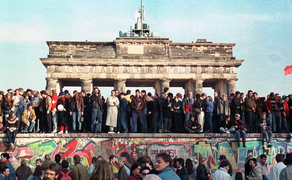 12. Жители Западного Берлина продолжают сидеть на Берлинской стене перед Бранденбургскими воротами 10 ноября 1989 года. (REUTERS/David Brauchli)