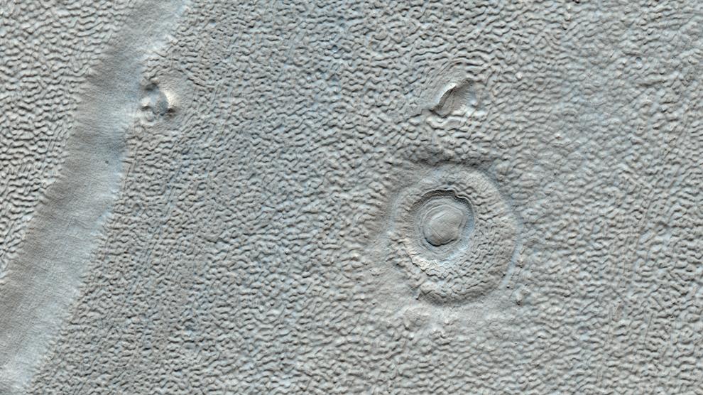 12. На этом снимке вы видите линованные отложения и обломки в долине в регионе Deuteronilus Mensae. Дно долин в этом регионе демонстрируют сложные линии небольших ямок и зубцов, часто называемых «линованные долинные отложения». Причина такой текстуры не совсем понятна, это может быть результат богатой льдами почвы или потери льда из-за высушивания. (NASA/JPL/University of Arizona)