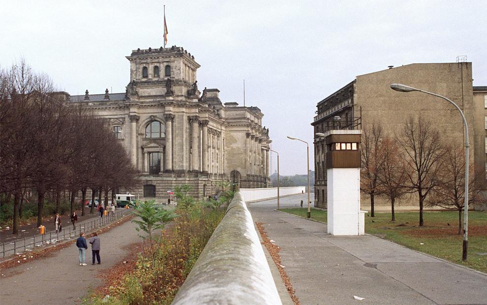 13. На этом фото здание немецкого Рейхстага (слева) с Берлинской стеной 10 ноября 1989 года. (GERARD MALIE/JOHN MACDOUGALL/AFP/Getty Images)