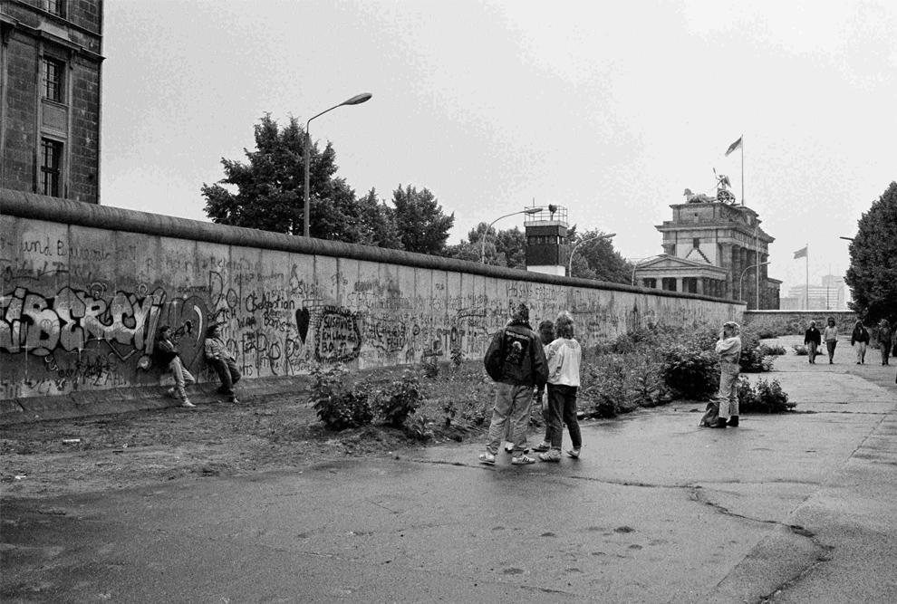 14. На этом снимке два молодых человека позируют у Берлинской стены у Бранденбургских ворот в Берлине 6 июня 1989 года. (REUTERS/Fabrizio Bensch)
