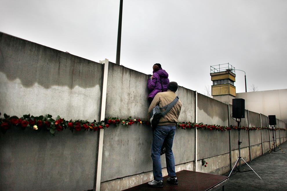 17. Среди роз, оставленных посетителями, парочка заглядывает через шесть оставшихся частей Берлинской стены в так называемую «смертельную зону», где солдатам Восточной Германии приказали расстреливать всех, кто попытается бежать в Западный Берлин. Снимок был сделан у памятника на Бернауэр Штрассе в 20-ую годовщину падения стены 9 ноября 2009 года в Берлине, Германия. (Carsten Koall/Getty Images)