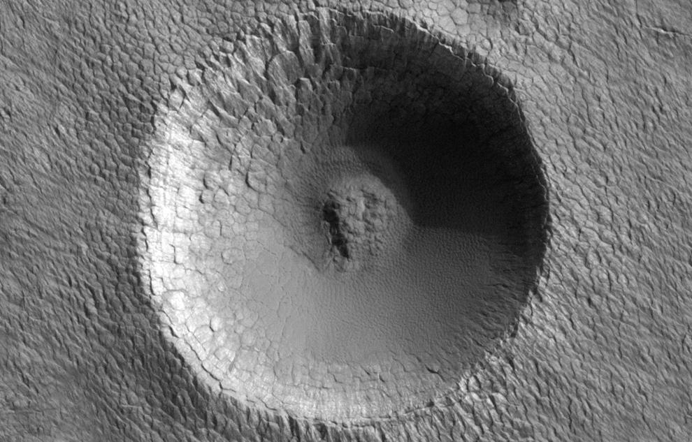 17. Метеоритный кратер на южном полярном слоистом отражении. Это небольшой (примерно 330 метров в диаметре) метеоритный кратер. Полярные слоистые отложения на Марсе считаются довольно молодыми, потому что на них нет более крупных кратеров и очень мало маленьких кратеров. (NASA/JPL/University of Arizona)