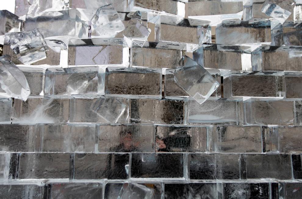 22. Люди смотрят на 3,5-метровую ледяную стену, которая является частью выставки под названием «Работа в прогрессе», представляющей Берлинскую стену, недалеко от немецкого посольства в Лондоне 9 ноября 2009 года. (AP Photo/Lefteris Pitarakis)