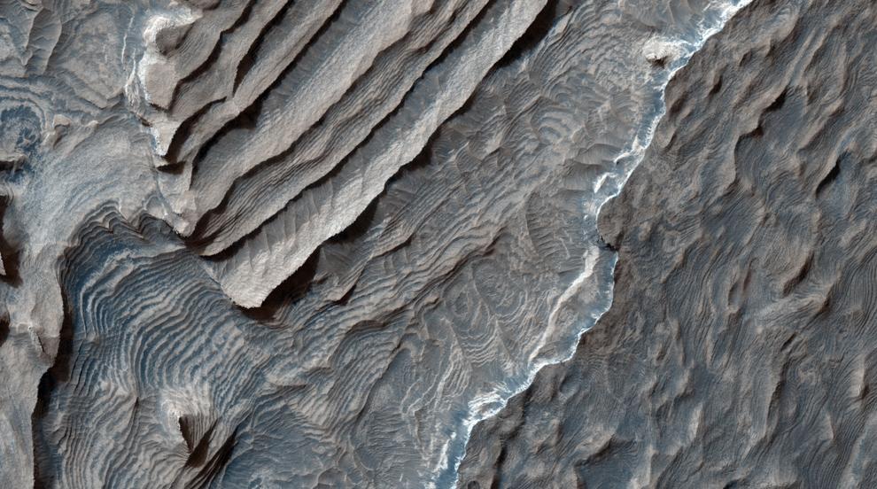 23. Светлые слоистые отложения вдоль кратера Бекерел – метеоритного кратера в регионе Терра Аравия. Отложения состоят из каскадных повторяющихся слоев, которые, похоже, составляют всего несколько метров в толщину. Поверхность отложений также кажется расколовшейся на несколько блоков в метр или больше длиной. (NASA/JPL/University of Arizona)