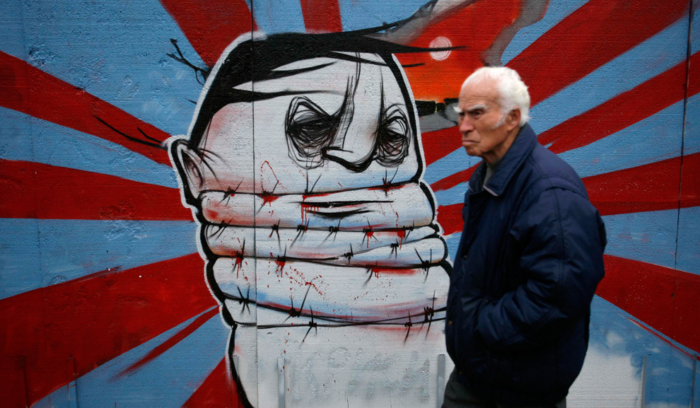 24. Мужчина проходит мимо граффити, символизирующего части Берлинской стены, на выставке в центральной Софии, Болгария, 9 ноября 2009 года. Арт-проект под названием «Стена 20 лет спустя» символизирует 20-ую годовщину падения стены и железного занавеса в Европе. (REUTERS/Stoyan Nenov)