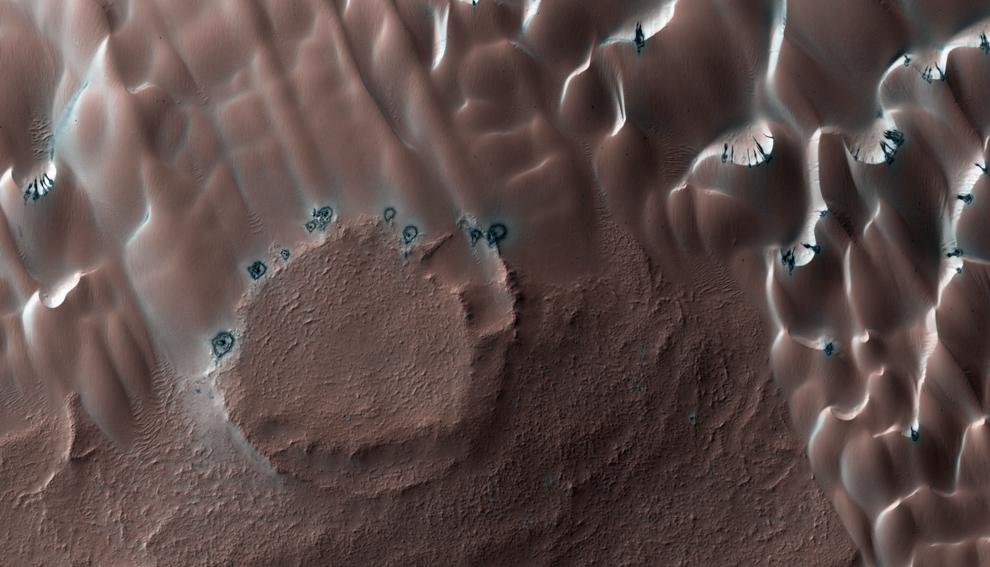 24. Оттаявшие дюны на севере. Северной зимой сезонная полярная «шапка» из сухого льда образовалась в северном полярном регионе. Эта «шапка» покрывает обширную площадь дюн на высоких северных широтах. Весной лед сублимирует (испаряется прямо в газ), и этот активный процесс ослабляет и двигает крошечные частички пыли. (NASA/JPL/University of Arizona)