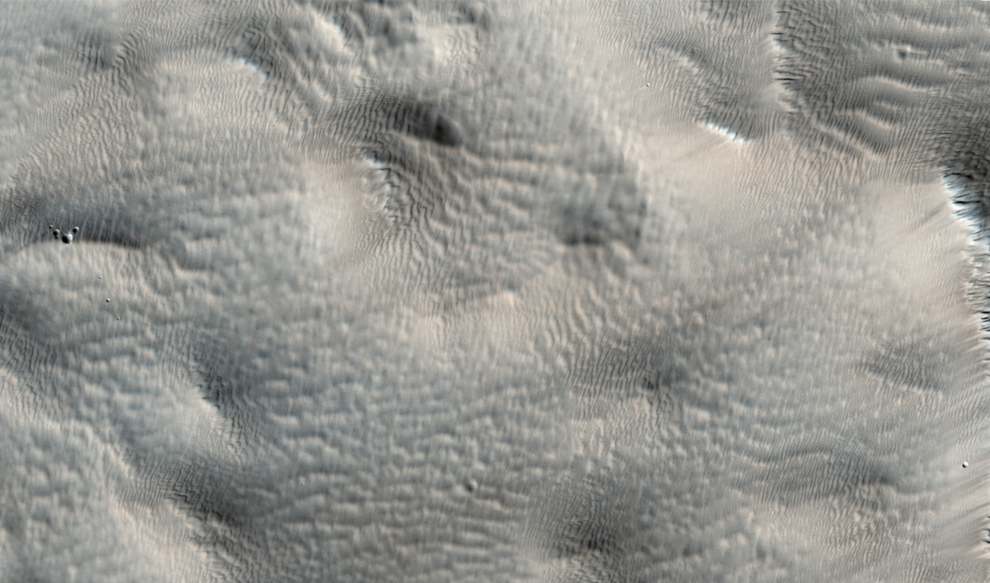 27. Размытый пейзаж недалеко от скопления вулканов Tharsis Montes. С первого взгляда может показаться, что некоторые части снимка не сфокусированы. Однако более четкие части говорят о том, что размытые области – не дефект фото, а невероятно гладкая поверхность. Эта гладкость образована толстым слоем пыли, покрывающим пейзаж. (NASA/JPL/University of Arizona)