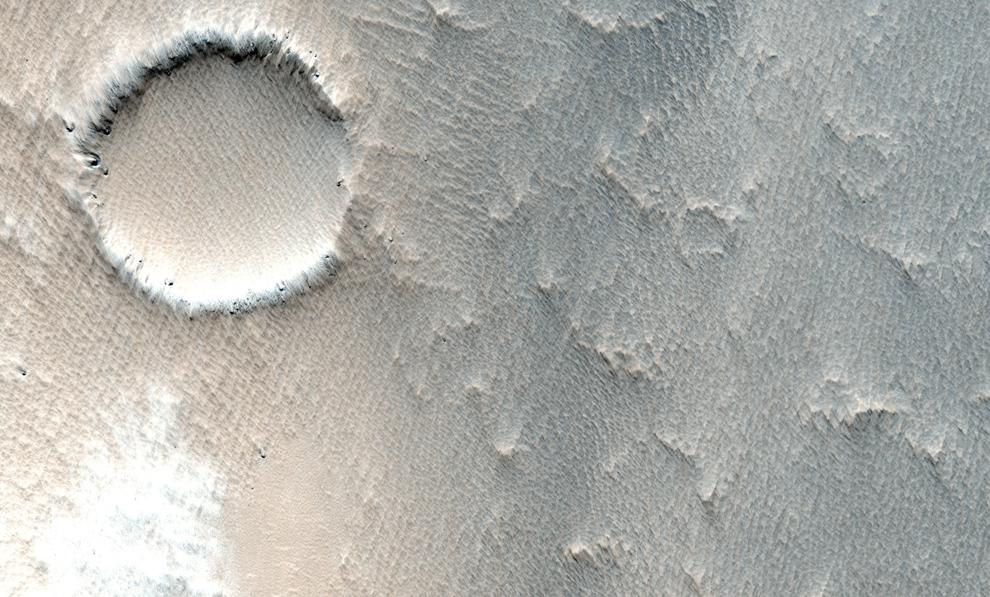 31. Небольшой кратер, частично зарытый в занесенных ветром выбросах более крупного кратера. (NASA/JPL/University of Arizona)