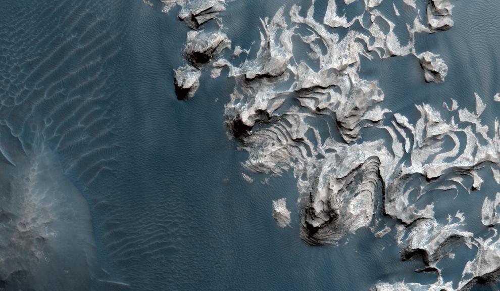 32. Крупное обнажение пород слоистой горы в области Хаос Ауреум, которая, очевидно, раскололась, оставив область неровных выступов и холмов. В отличие от многих выступов светлое обнажение пород демонстрирует отдаленные почти горизонтальные слои. Это могло остаться от крушения Хаоса. (NASA/JPL/University of Arizona)