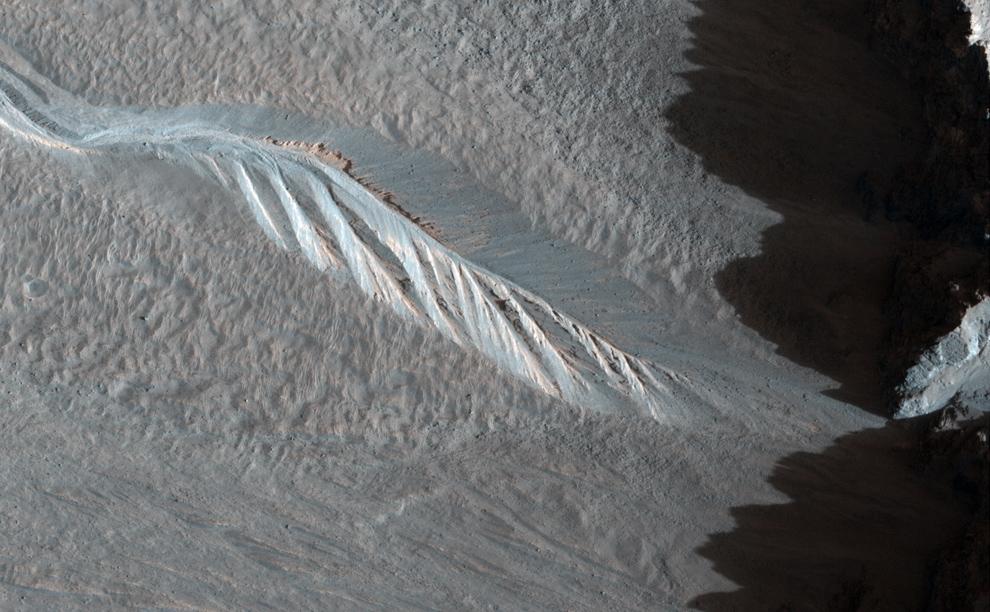 33. Канава вдоль внешней стены Западного кратера Хейл, затемненная возвышающимся краем кратера. (NASA/JPL/University of Arizona)
