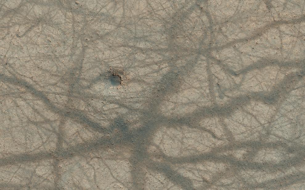 35. Небольшой метеоритный кратер, ямные выступы и перекрестное смешение следов пыльного вихря на марсианской поверхности. (NASA/JPL/University of Arizona)