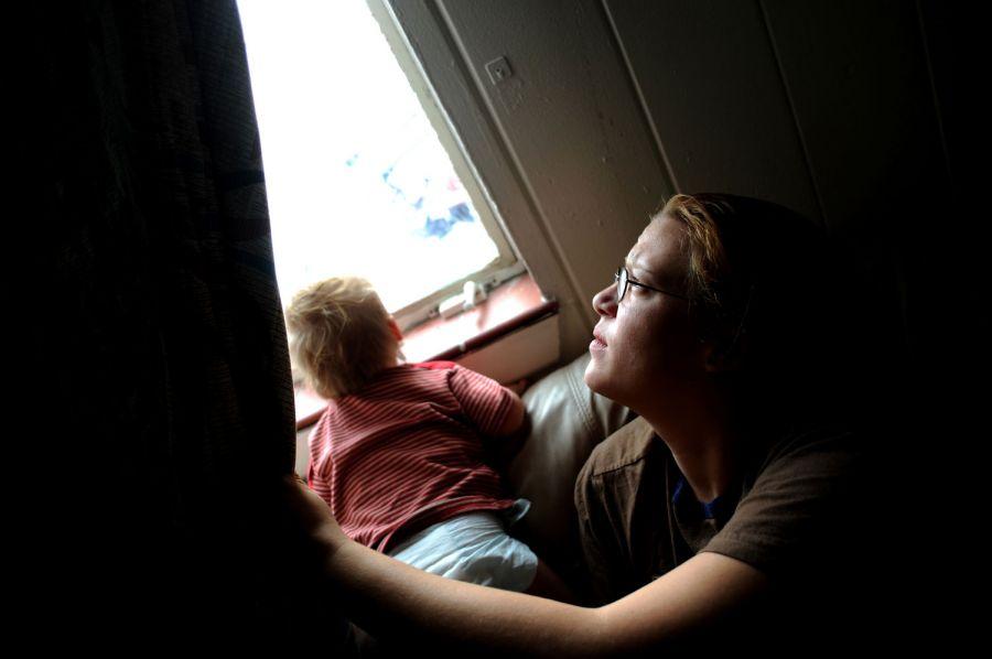 2. 24-летняя Сабрина Лэки смотрит в окно в мотеле «Sand and Sage». «Это, конечно, нелегкие времена, - говорит Лэки.- Думаю, нам повезло, что мы здесь. Здесь прилично». «Здесь» - это мотель «Sand & Sage» на улице Ист Колфакс Авеню в нескольких домах от субботнего стриптиз клуба. Лэки живет здесь уже три месяца, она платит 200 долларов в неделю за свою комнатку.
