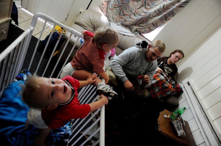 5. Джефф и Сабрина Лэки в снимаемой ими комнате мотеля «Sand & Sage». Их мальчики-близнецы играют в детской кроватке.