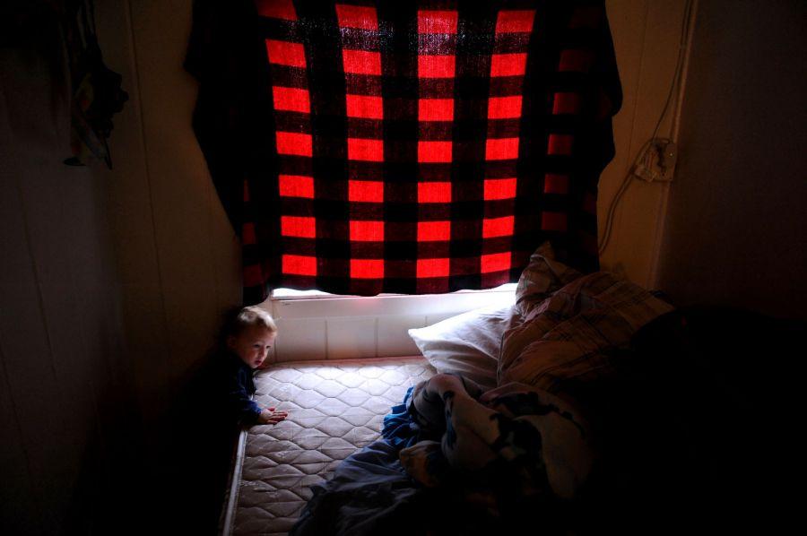 6. 17-месячный Адам Лэки ползает и играет в комнате, которую его родители снимают в мотеле «Sand & Sage» на улице Ист Колфакс Авеню в Денвере.