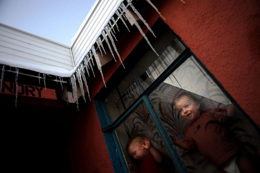 8. 17-месячные близнецы Джозеф (слева) и Адам Лэки выглядывают из окна, завешенного старым одеялом, в мотеле «Sand & Sage» на Ист Колфакс Авеню в Денвере после снежной ночи. С тех пор как их отец Джефф потерял работу, семья три месяца скиталась по мотелям, прежде чем остановиться в «Sand & Sage».