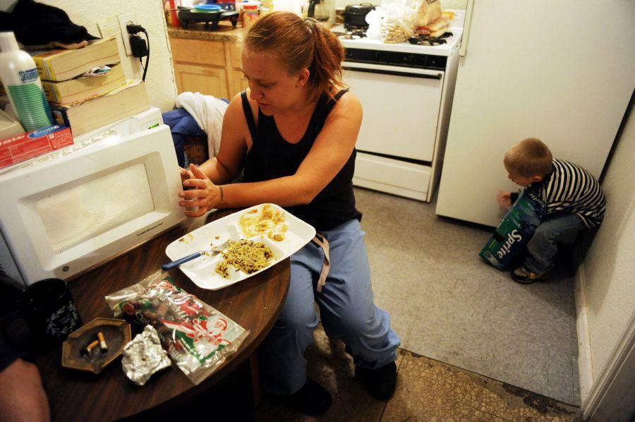 12. Джеми Роуз достает еду из микроволновой печи, пока ее сын Алекс играет с коробкой из-под газировки на кухне в снимаемом ими номере мотеля «Triangle T Motel» в Коммерс Сити. Колорадо. Семья Рауз, состоящая из Джеми, ее мужа Уиллиса и их сына Рики, живут в мотеле «Triangle T». Они платят за номер 247 долларов в неделю. Ранеше они жили в мотеле «Clear View» в Коммерс Сити, но его закрыли за нарушение санитарных норм.