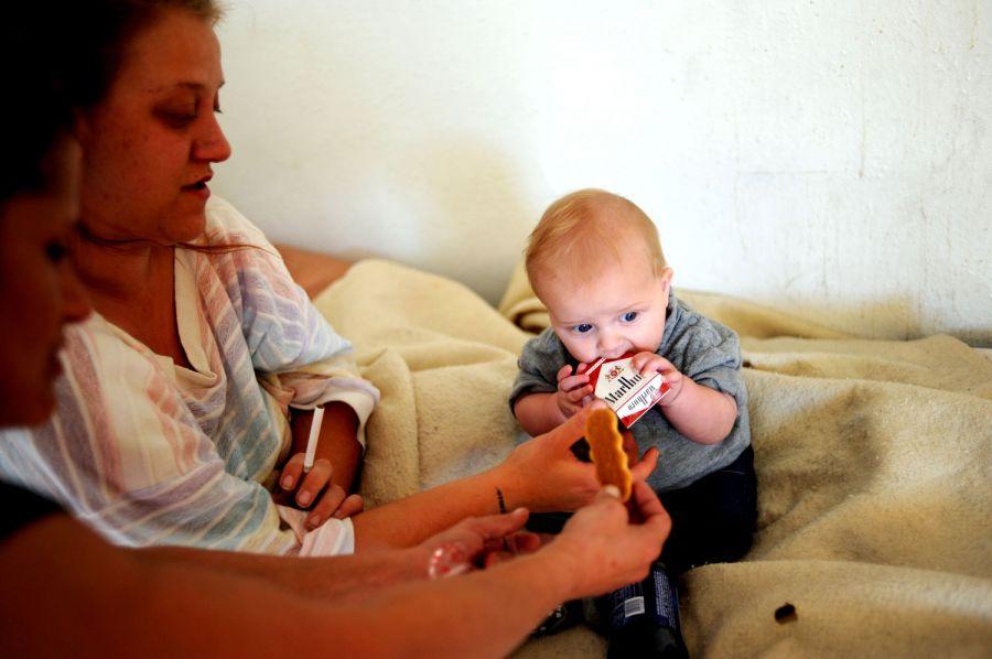 14. 5-месячный Рики Рауз играет с пачкой сигарет своей матери на кровати в номере, снимаемом семьей в мотеле «Triangle T Motel».