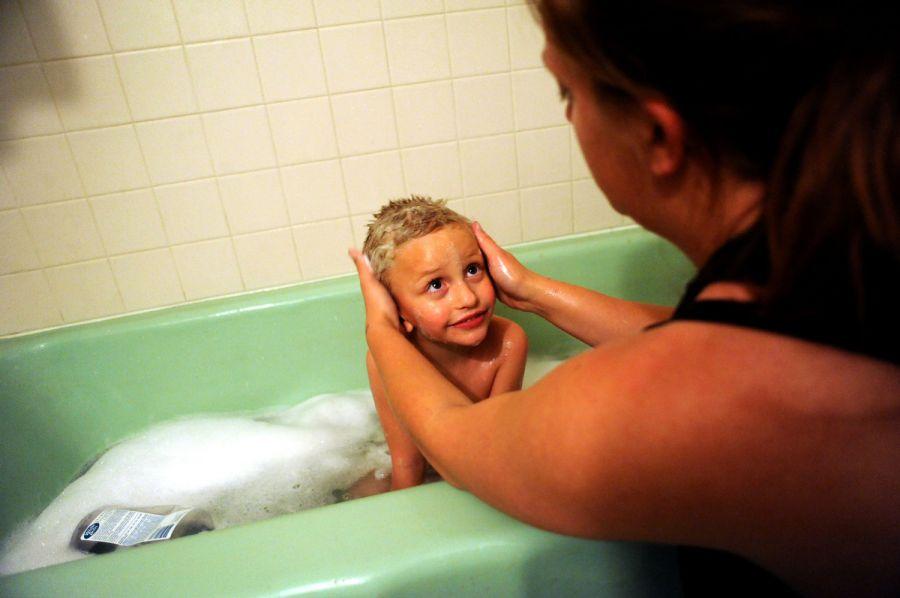 15. Джеми Рауз купает своего 5-летнего сына Алекса в ванне номера мотеля «Triangle T Motel».
