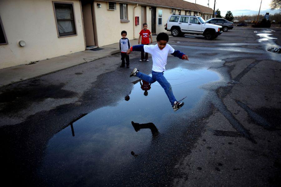 23. Братья и сестры (слева направо) 5-летний Рэйлон Тайсон, 8-летняя Кайла Тайсон и 7-летний генри Уэдделпрыгают через лужи на стоянке мотеля «Triangle T Motel» в Коммерс Сити. Семья переехала в мотель после того, как мотель «Clear View», в котором они жили, закрыли из-за нарушения санитарных норм.