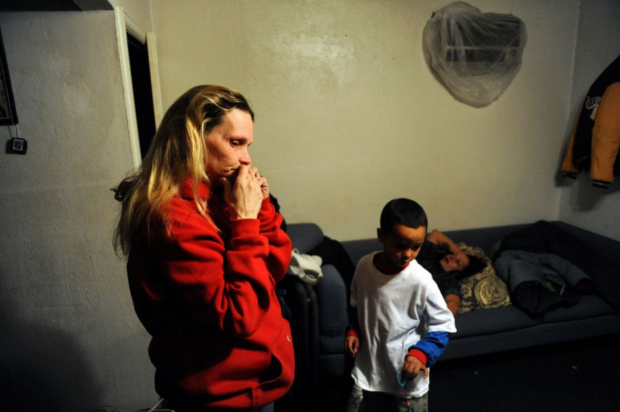 24. Дебби Блевинс (слева) стоит в номере мотеля «Triangle T Motel», в котором она живет с дочерью и тремя внуками. Блевинс поддерживает свою дочь и внуков и платит за номер каждую неделю. Они с дочерью спят на одной кровати, в то время как их дети спят на полу.