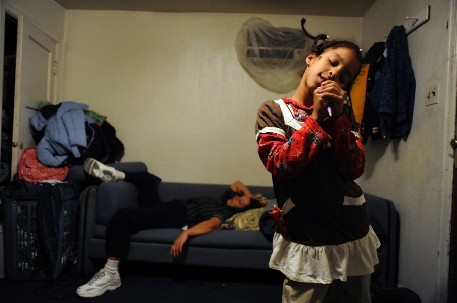 25. 8-летняя Кайла Тайсон делает вид, что поет в микрофон в номере мотеля «Triangle T Motel». На заднем плане - на диване спит родственник семьи.