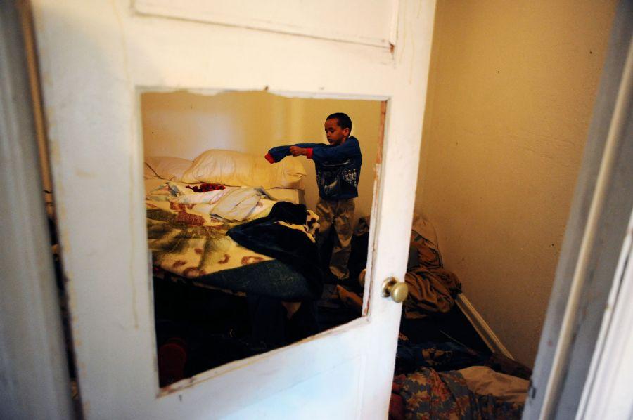 26. 5-летний Рэйлон Тайсон одевается в комнате мотеля «Triangle T Motel». Семья собирается идти за рождественскими гирляндами в парк Сивик Центр в Денвере.