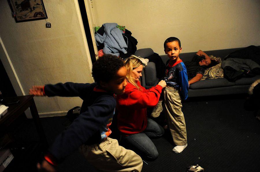 27. Бабушка Дебби Блевинс помогает Рэйлону Тайсону надеть штаны, в то время как его брат Генри играет в тесной комнатке мотеля «Triangle T Motel».