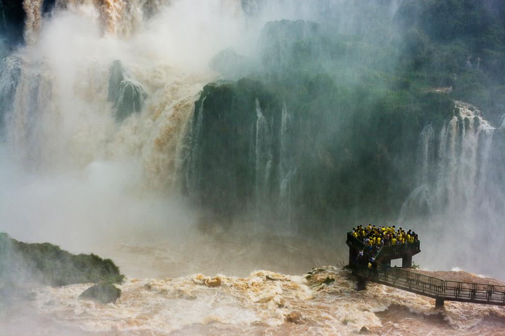 8. На мой второй день посещения удивительных водопадов Игуазу на Бразильской стороне мне пришлось заменить в фотоаппарате объектив с широкоугольного, на телеобъектив. До моего прибытия дожди шли 10 дней, и поэтому водопады были особенно великолепны. Стоя на возвышенной смотровой площадке, я смог делать этот снимок группы туристов, которые стояли, как вкопанные, что еще больше показало настоящую силу и размер водопадов. (Photo and caption by Ian Kelsall)