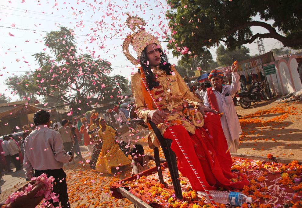 12. Мужчину в костюме индийского бога Рамы осыпают цветами во время парада в Пушкаре в четверг 29 октября 2009 года. (AP Photo/Kevin Frayer)