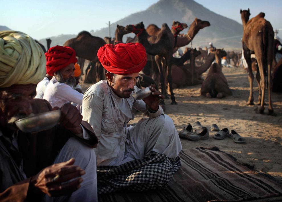 22. Мужчины пьют утренний чай в ожидании клиентов на ярмарке Пушкар Мела рано утром в среду 28 октября 2009 года. (AP Photo/Kevin Frayer)